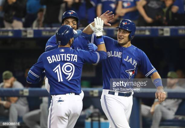 Jose Bautista of the Toronto Blue Jays is congratulated by Luke Maile and Devon Travis after hitting a threerun home run in the fifth inning during...