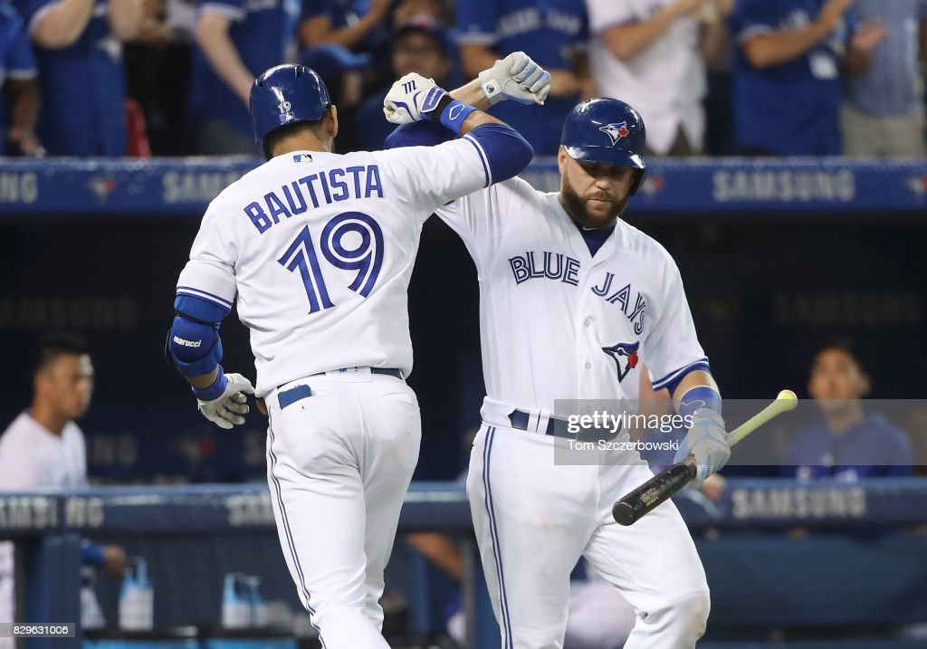 Jose Bautista #19 of the Toronto Blue Jays is congratulated by Russell Martin #55 after hitting a solo home run in the seventh inning during MLB game action against the New York Yankees at Rogers Centre on August 10, 2017 in Toronto, Canada.