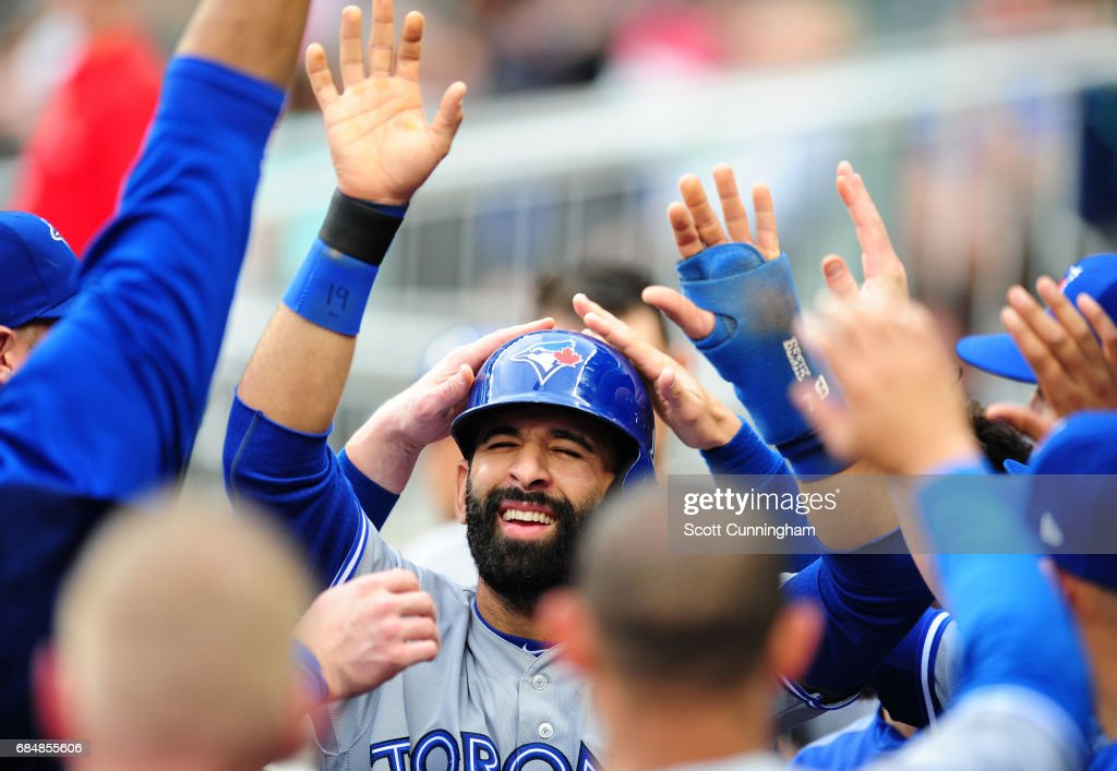 Jose Bautista #19 of the Toronto Blue Jays is congratulated by teammates after scoring a first inning run against the Atlanta Braves at SunTrust Park on May 18, 2017 in Atlanta, Georgia.