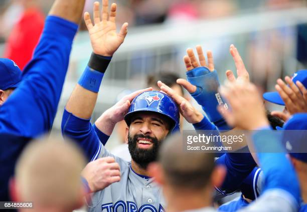 Jose Bautista of the Toronto Blue Jays is congratulated by teammates after scoring a first inning run against the Atlanta Braves at SunTrust Park on...