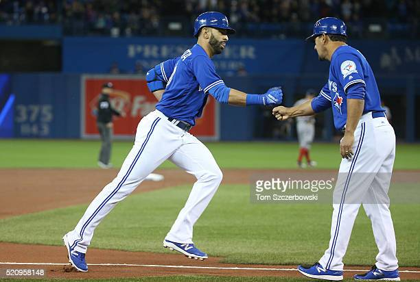 Jose Bautista of the Toronto Blue Jays is congratulated by third base coach Luis Rivera after hitting a tworun home run in the first inning during...