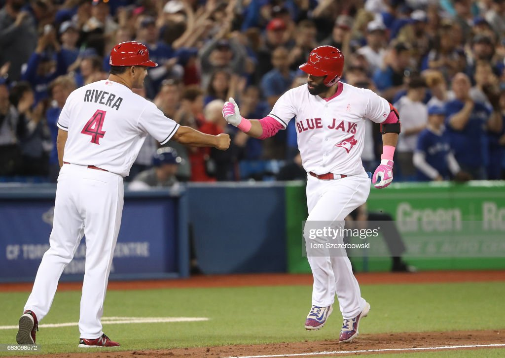 Jose Bautista #19 of the Toronto Blue Jays is congratulated by third base coach Luis Rivera #4 after hitting a three-run home run in the seventh inning during MLB game action as Nick Vincent #50 of the Seattle Mariners reacts at Rogers Centre on May 13, 2017 in Toronto, Canada.