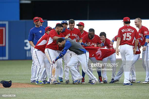Jose Bautista of the Toronto Blue Jays is congratulated on his gamewinning hit by teammates in the ninteenth inning during MLB game action against...