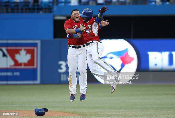 Jose Bautista of the Toronto Blue Jays is congratulated on his gamewinning hit by Melky Cabrera in the ninteenth inning during MLB game action...