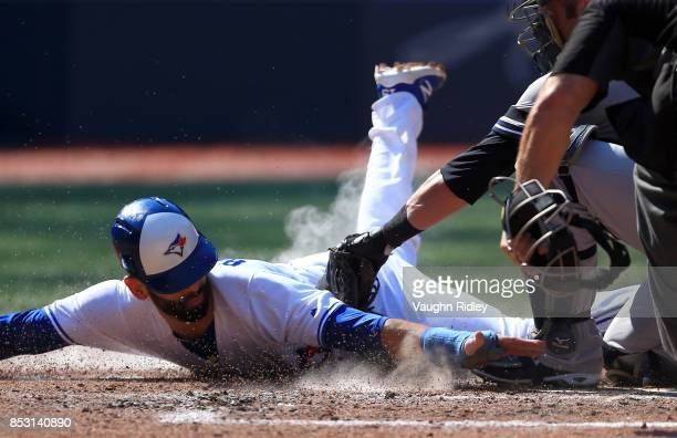 Jose Bautista of the Toronto Blue Jays is tagged out at home plate by Austin Romine of the New York Yankees in the fourth inning during MLB game...