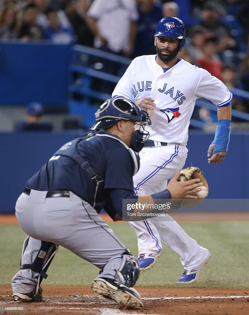 Jose Bautista #19 of the Toronto Blue Jays is thrown out at home plate in the second inning during MLB game action as Jesus Sucre #2 of the Seattle Mariners fields the throw and prepares to tag him out on September 22, 2014 at Rogers Centre in Toronto, Ontario, Canada.