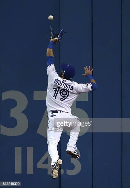Jose Bautista of the Toronto Blue Jays misses an RBI double hit by Mike Napoli of the Cleveland Indians in the first inning during game three of the...