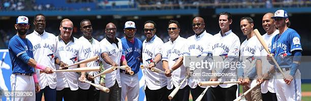 Jose Bautista of the Toronto Blue Jays poses beside former players John Mayberry and Ernie Whitt and Tony Fernandez and Lloyd Moseby and current...
