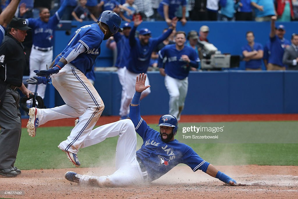 Jose Bautista #19 of the Toronto Blue Jays slides into home plate to score the winning run as Jose Reyes #7 celebrates in the ninth inning during MLB game action against the Houston Astros on June 7, 2015 at Rogers Centre in Toronto, Ontario, Canada.