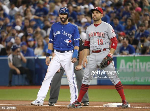 Jose Bautista of the Toronto Blue Jays stands on first base as Joey Votto of the Cincinnati Reds holds him on in the first inning during MLB game...