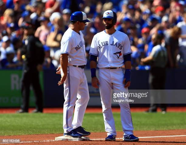 Jose Bautista of the Toronto Blue Jays talks to third base coach Luis Rivera during a MLB game against the New York Yankees at Rogers Centre on...