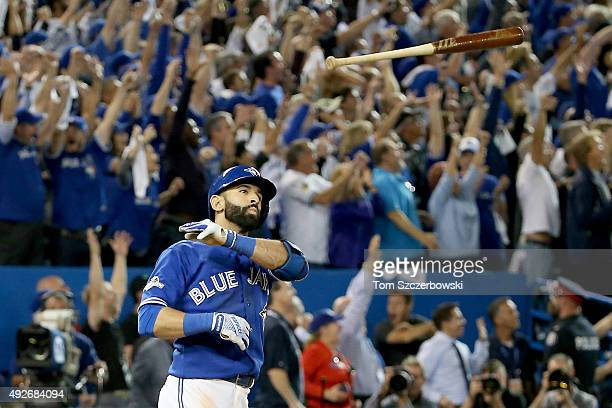 Jose Bautista of the Toronto Blue Jays throws his bat up in the air after he hits a three-run home run in the seventh inning against the Texas...