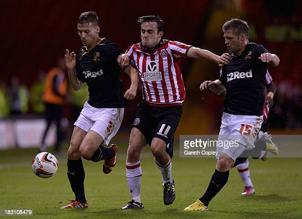 Jose Baxter of Sheffield Utd gets between Mat Sadler and Dannie Bulman of Crawley Town during the Sky Bet League One match between Sheffield United...