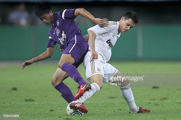 Jose Callejon of Real Madrid competes the ball with Nie Tao of Tianjin Teda during the preseason friendly match between Tianjin Teda and Real Madrid...