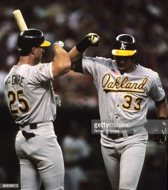 Jose Canseco of the Oakland Athletics is congratulated by Mark McGwire of the Oakland Athletics after hitting a home run against the Cincinnati Reds...