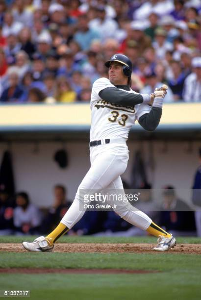 Jose Canseco of the Oakland Athletics watches the flight of the ball as he follows through on a swing during a 1991 MLB season game against the...