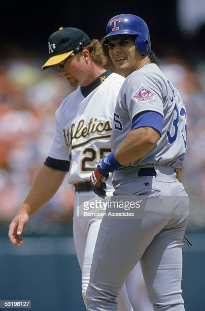Jose Canseco of the Texas Rangers walks on the field with Mark McGwire of the Oakland Athletics during a 1993 season game Jose Canseco played for the...