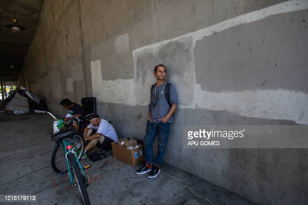Jose Cardenas 40 yearsold stands under the bridge of the 110 Freeway at 37th Street to recharge his phone during the novel Coronavirus COVID19...