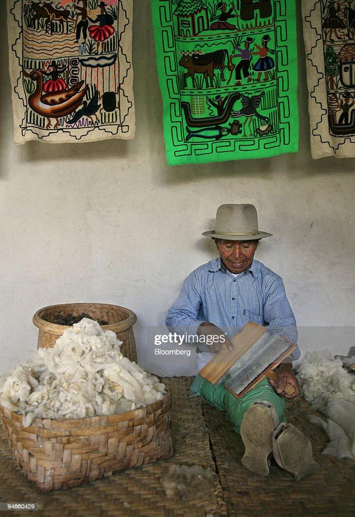 Jose Carlos de la Torre sits carding alpaca wool inside his : News Photo