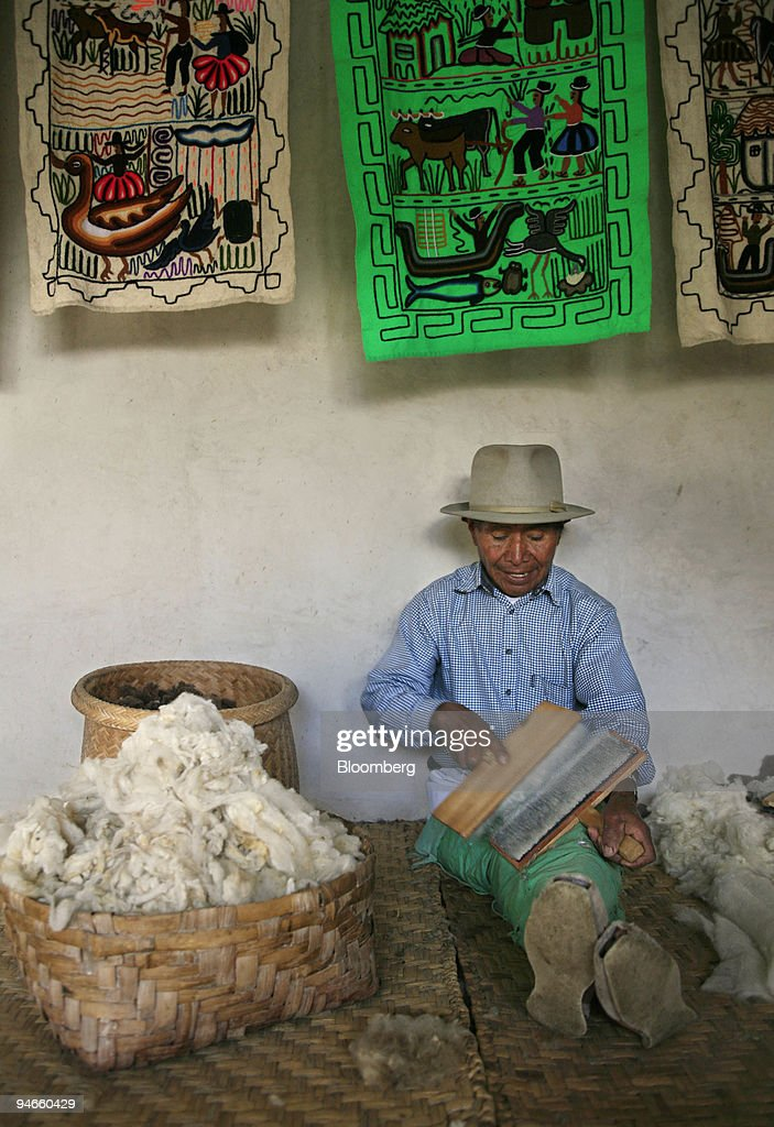 Jose Carlos de la Torre sits carding alpaca wool inside his workshop in Carabuela, Ecuador, Wednesday, November 22, 2006. Carding is the last step in preparing the wool for spinning which cleans, separates, and straightens the wool fibers. The finished batt or rolag of soft, fluffy wool makes spinning easier.