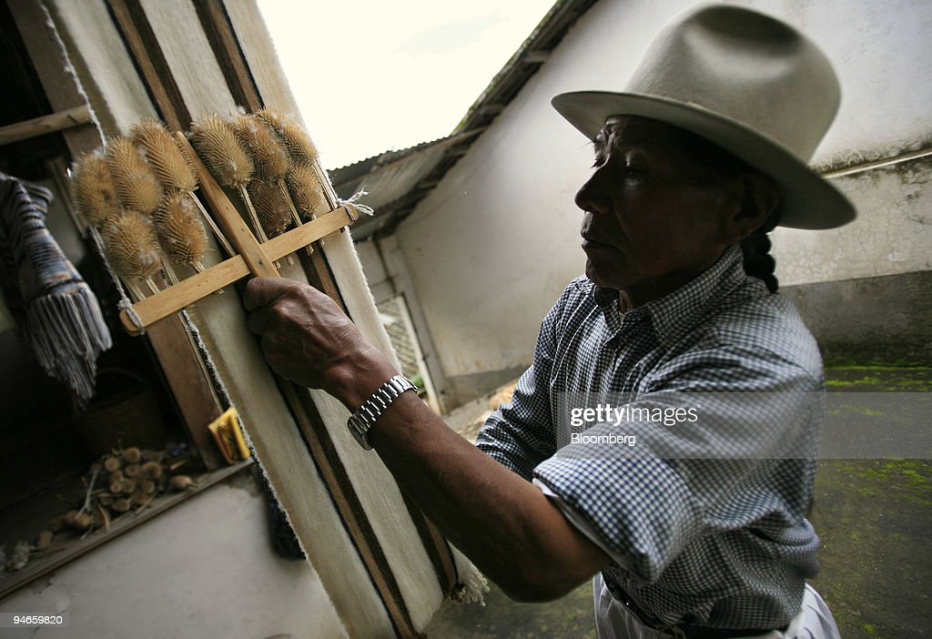 Jose Carlos de la Torre uses a brush made up of teasel to smooth an alpaca wool scarf inside his workshop in Carabuela, Ecuador, Wednesday, November 22, 2006.