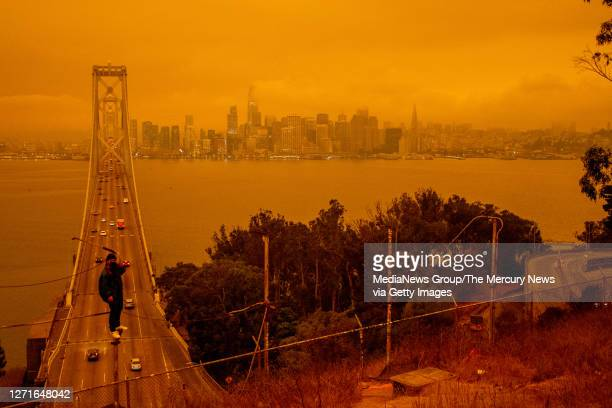Jose Castillo has his photo taken with the Bay Bridge and the San Francisco skyline in the background by his friend Laito Miyake, both of San...