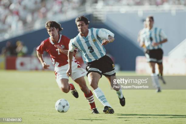 Jose Chamot of Argentina makes a run with the ball ahead of Emil Kostadinov of Bulgaria during play between Argentina and Bulgaria in their 1994 FIFA...