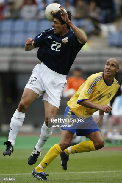 Jose Chamot of Argentina stops the ball reaching Henrik Larsson of Sweden during the FIFA World Cup Finals 2002 Group F match played at the Miyagi...