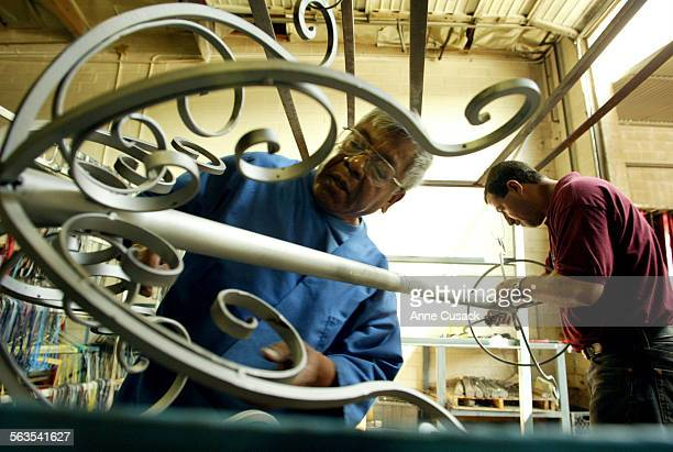 Jose Colindres and Martin Romo clean the hat rack after sand blasting and before it is sprayed wsith powderA wrought iron hat rack is transformed...