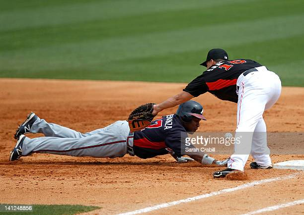 Jose Constanza of the Atlanta Braves dives safely back to first base as the ball passes Gaby Sanchez of the Miami Marlins during a game against the...