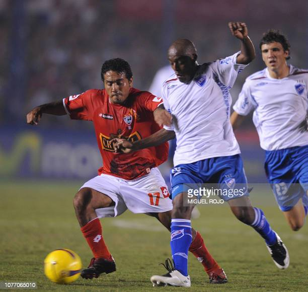 Jose Corcuera of Peru's Cienciano vies for the ball with Oscar Morales of Uruguays Nacional during their Libertadores Cup football match in...