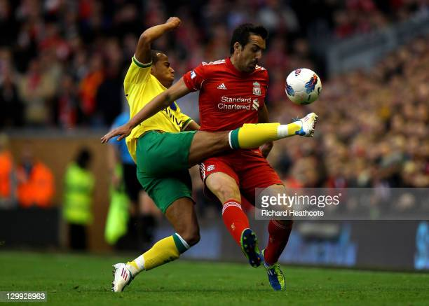 Jose Enrique of Liverpool is challenged by Elliott Bennett of Norwich City during the Barclays Premier League match between Liverpool and Norwich...
