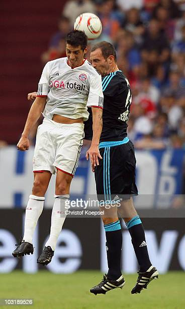 Jose Ernesto Sasa of Bayern and Christoph Metzelder of Schalke go up for a header during the LIGA total Cup 2010 final match between FC Bayern...