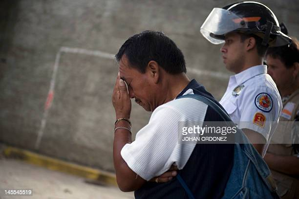 Jose Fernandez gestures as he looks at the body of his friend and 'mototaxi' driver William Cual who was murdered and burned by alleged gang members...