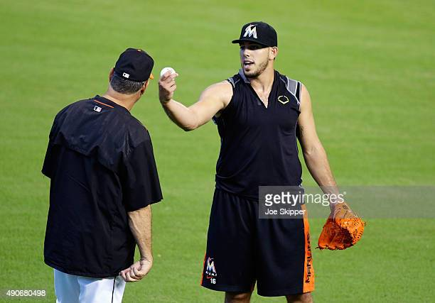 Jose Fernandez of the Miami Marlins speaks with pitching coach Chuck Hernandez as Fernandez threw in the outfield before the Miami Marlins met the...
