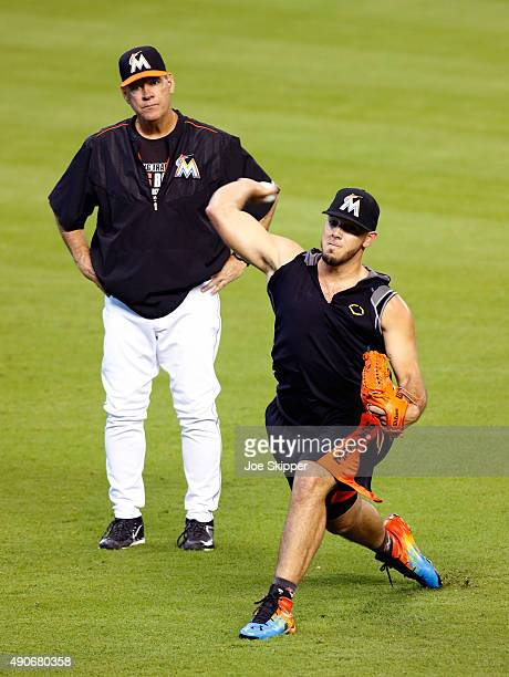 Jose Fernandez of the Miami Marlins throws as pitching coach Chuck Hernandez looks on in the outfield before the Miami Marlins met the Atlanta Braves...