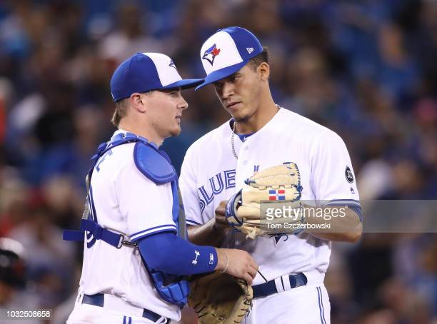 Jose Fernandez of the Toronto Blue Jays talks with Reese McGuire on the mound as he comes in to pitch in the fifth inning during MLB game action...