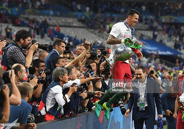 Jose Fonte of Portugal holds the Henri Delaunay trophy to celebrate with supporters after his team's 10 win against France in the UEFA EURO 2016...