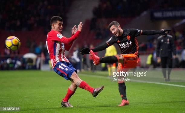 Jose Gaya of Valencia CF crosses the ball past Angel Correa of Atletico de Madrid during the La Liga match between Atletico Madrid and Valencia at...