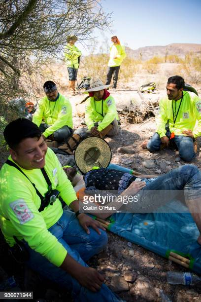 Jose Genis helps firsttime volunteer Jason Bechtel after he experiences signs of heat stroke during Aguílas del Desierto search and rescue crew's...