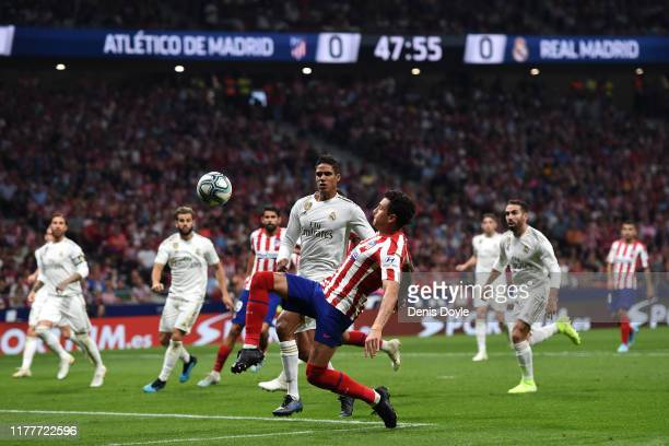 Jose Gimenez of Atletico Madrid battles for the ball with Raphael Varane of Real Madrid during the Liga match between Club Atletico de Madrid and...