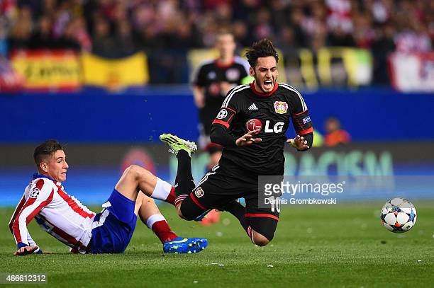 Jose Gimenez of Atletico Madrid fouls Hakan Calhanoglu of Bayer Leverkusen during the UEFA Champions League round of 16 match between Club Atletico...