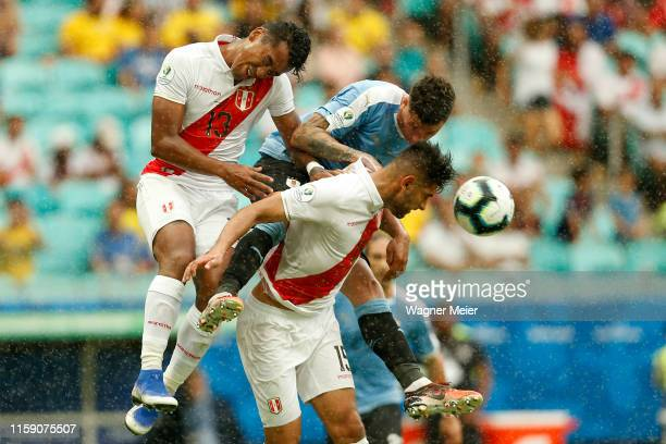 Jose Gimenez of Uruguay heads the ball against Renato Tapia and Carlos Zambrano of Peru during the Copa America Brazil 2019 quarterfinal match...
