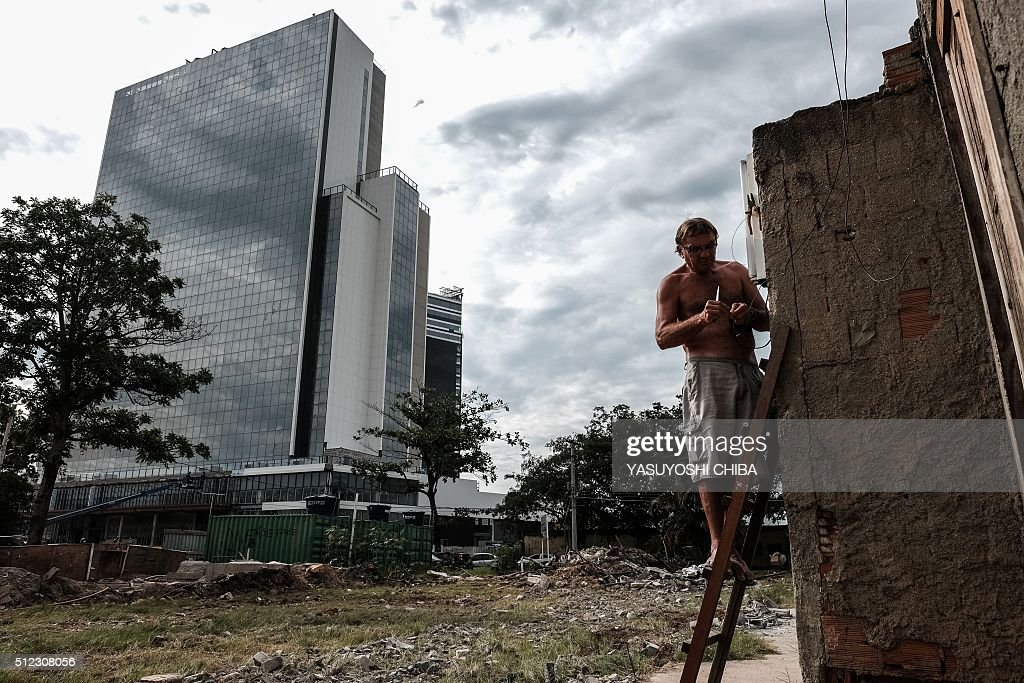 Jose Gomes, 59, Does Maintenance Tasks In His House At Vila Autodromo Next  To The Construction Site Of The Olympic Park For Rio 2016 Olympic Games In  Rio De ...