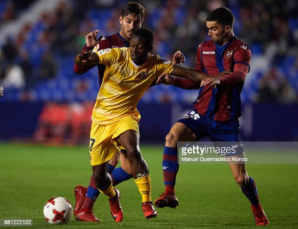 Jose Gomez Campana and Sergio Postigo of Levante competes for the ball with Marlos Moreno of Girona during the Copa del Rey Round of 32 Second Leg...