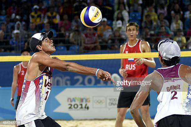 Jose Gregorio Gomez and Rolando Hernandez of Venezuela compete with Oleg Stoyanovskiy and Artem Larzutkin of Russia in the Men's Beach Volleyball...