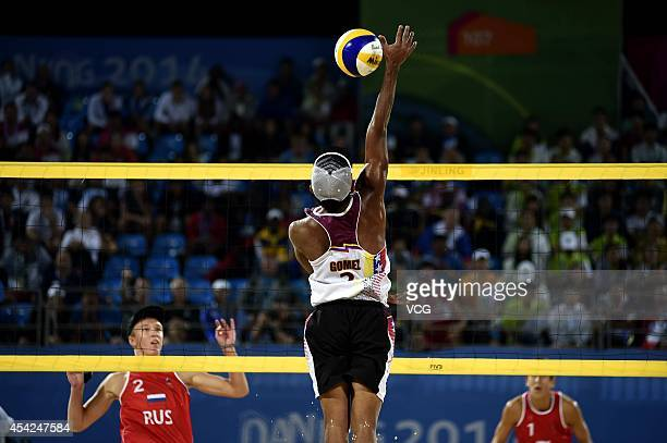 Jose Gregorio Gomez of Venezuela competes with Oleg Stoyanovskiy and Artem Larzutkin of Russia in the Men's Beach Volleyball Final match on day...