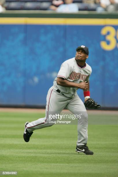 Jose Guillen of the Washington Nationals attempts a catch against the Atlanta Braves at Turner Field on April 13, 2005 in Atlanta, Georgia. The...