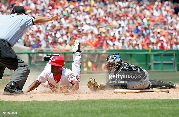 Jose Guillen of the Washinton Nationals slides safely into home as catcher Gregg Zaun of the Toronto Blue Jays applies the tag late during the third...