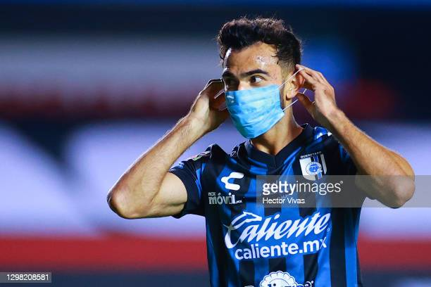Jose Gurrola of Queretaro celebrates putting a face mask after scoring the first goal of his team during the 3rd round match between Queretaro and...